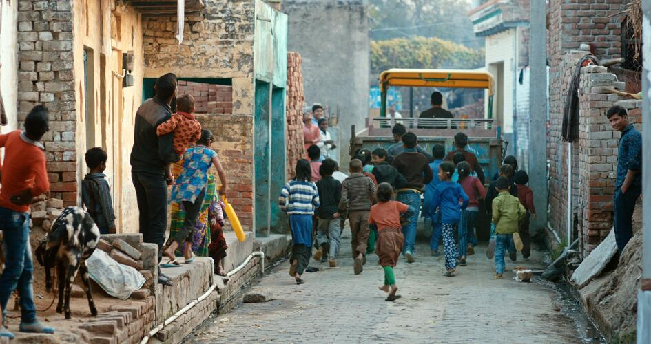 Children following a delivery truck in a street in India