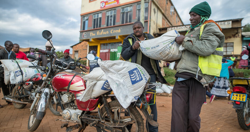 Two African men loading fertilizer bags on motorbike